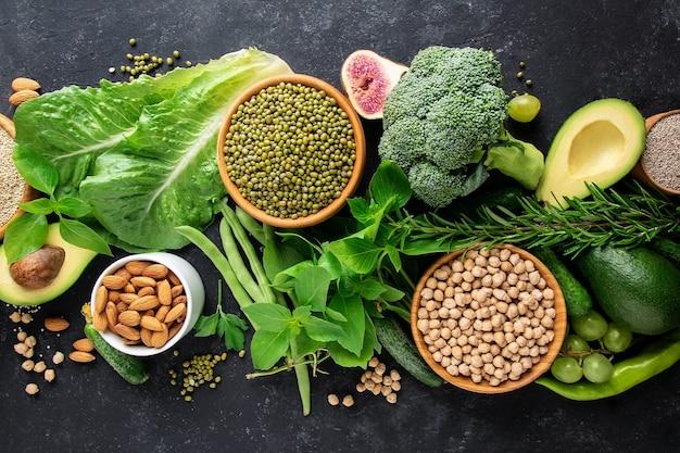 Свежие здоровые вегетарианские блюда на черном фоне.