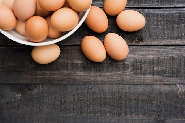 Свежее куриное яйцо в белой миске и 6 куриных яиц снаружи на деревянном столе черного цвета