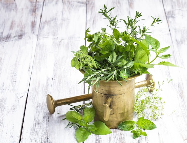 Fresh herbs in the copper mortar on the shabby wooden table
