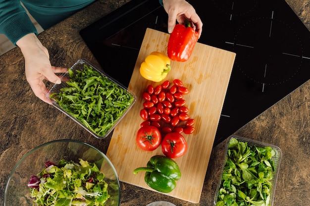 여자 주부의 신선한 허브 손입니다. 신선한 야채와 채소의 샐러드를 준비하는 엄마 아내 체리 토마토 rucola 고추. 가정 생활. 건강 식품 개념