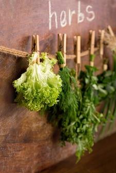Свежие травы, висящие на деревянных фоне. тимьян, базилик, орегано, петрушка.