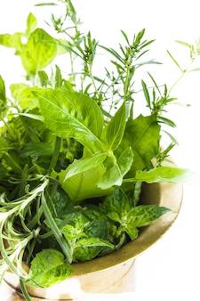 Свежие травы в медной ступке на столе