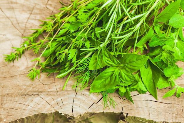Свежие травы на открытом воздухе на деревянных фоне