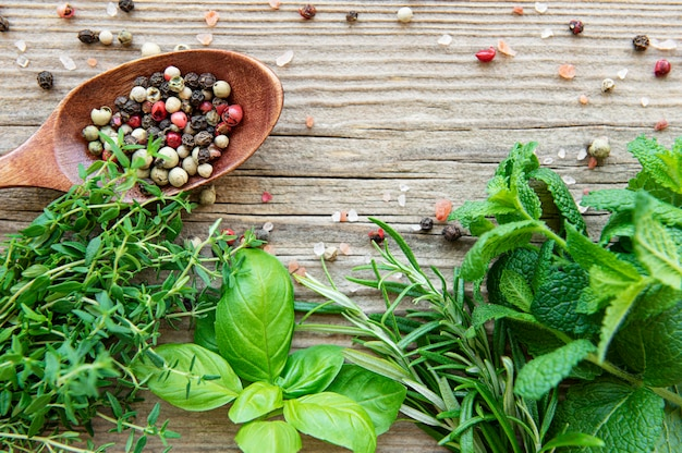 Fresh herbs and spices on wooden background top view