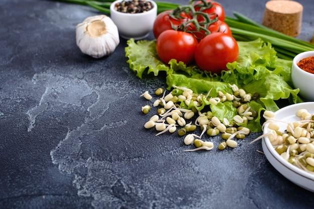 신선한 허브 야채 조미료와 콩이 함께 그룹화되어 돌 표면에 놓여 있습니다.
