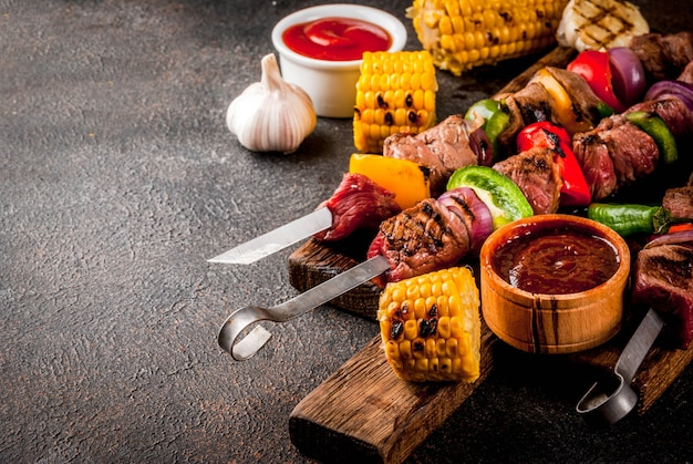Fresh, home-cooked on the grill fire meat beef shish kebab with vegetables and spices, with barbecue sauce and ketchup