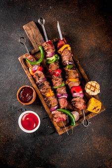 Свежий домашний шашлык из мяса на гриле с овощами и специями, с соусом барбекю и кетчупом,