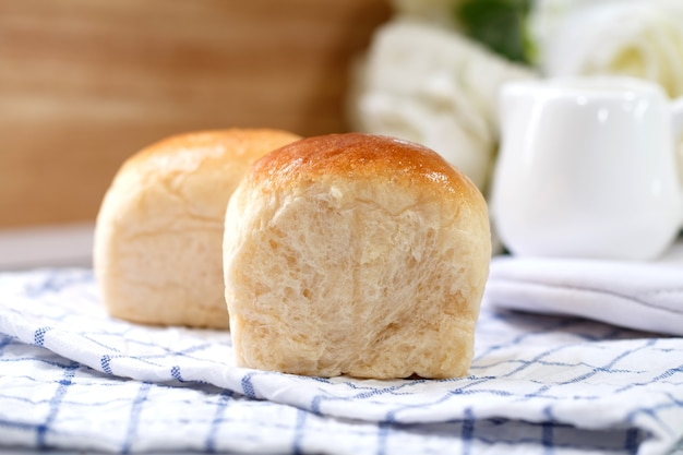 Fresh home made bread on white table background with napkin.