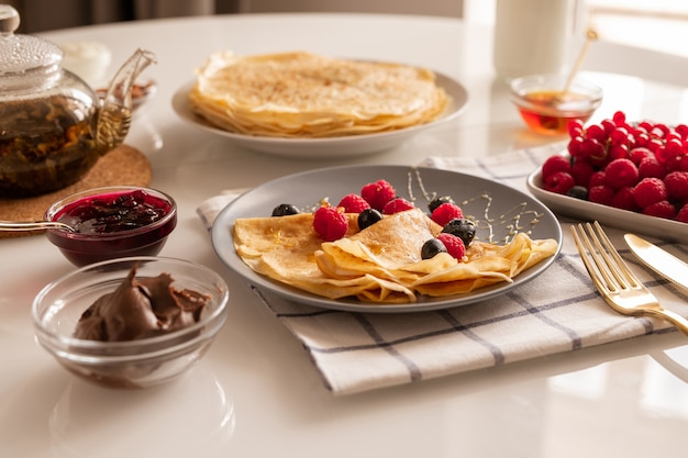 Fresh homemade appetizing crepes with berries and honey on plate, bowls with cherry jam and chocolate cream, teapot and ripe raspberries