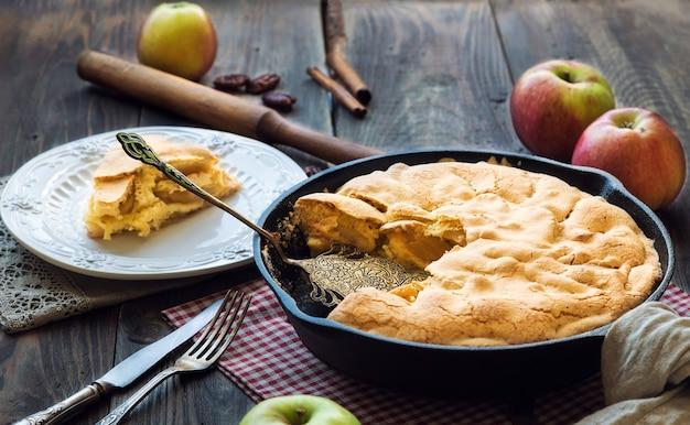 素朴な木製のテーブルの上に鉄のフライパンで焼いた新鮮な自家製アップルパイ。