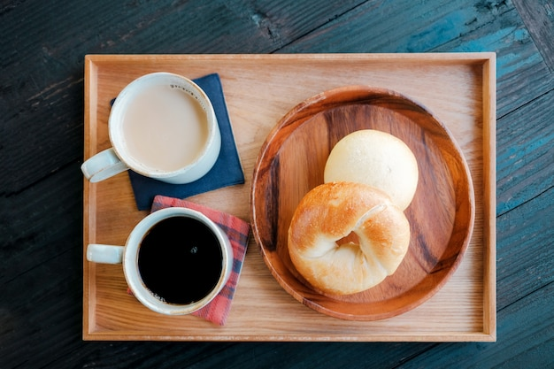 Fresh homemade bagel bread and hot coffee, milk tea on wooden tray in the morning