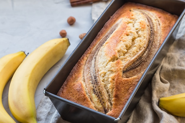 Fresh homemade banana bread in baking form on light concrete surface.
