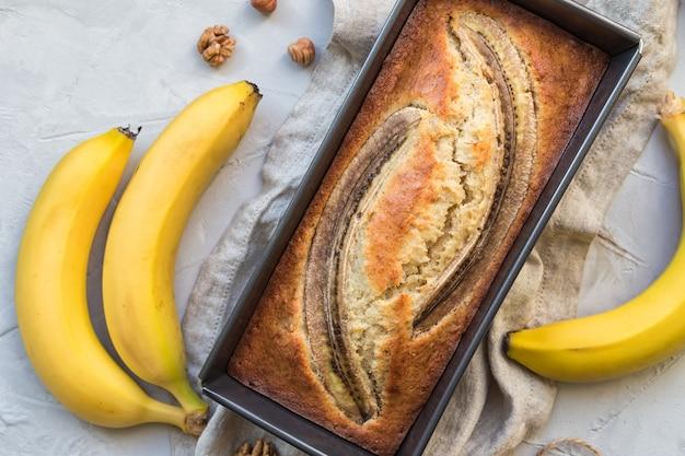 Fresh homemade banana bread in baking form on light concrete