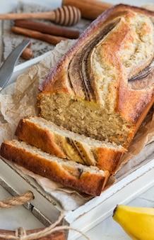 Свежий домашний банановый хлеб в белом деревянном подносе на легкой бетонной поверхности. выборочный фокус.