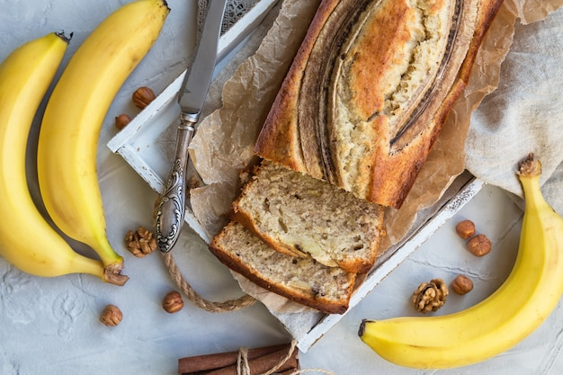 Свежий домашний банановый хлеб в белом деревянном подносе с ингредиентами на легкой бетонной поверхности. вид сверху.