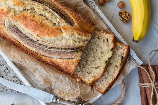 Fresh homemade banana bread in white wooden tray with ingredients on light concrete background
