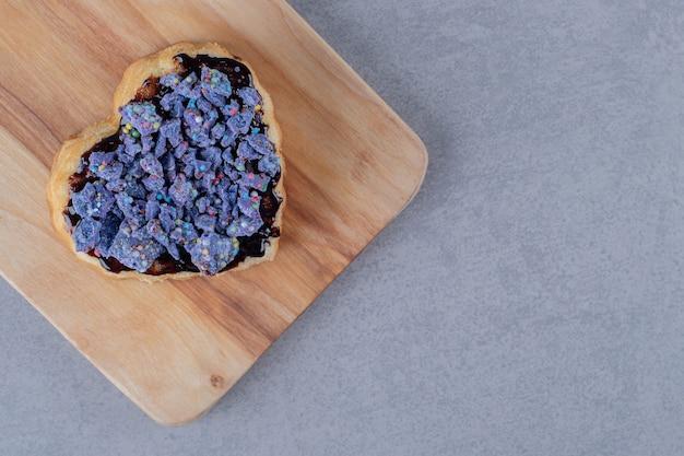 灰色の表面上の青い木の板に新鮮な自家製ブルーベリークッキー