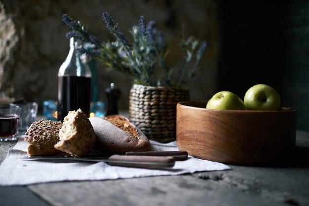 ナプキンに焼きたての自家製パンとナイフ、赤ワインとガラス製品、木製のテーブルに青リンゴと木製のボウルを朝食に提供