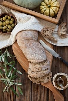 木製のまな板、オリーブオイル、オリーブ、カボチャ、オリーブの木の葉に焼きたての自家製パンチャバタ。