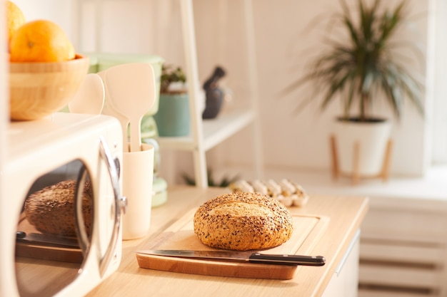 Свежий домашний хлеб на деревянном столе в интерьере кухни