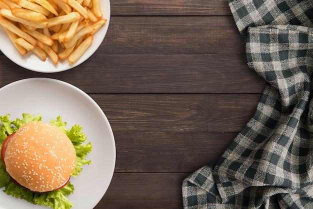 신선한 수 제 햄버거와 감자 튀김 나무 테이블에. 평면도, 복사 공간.