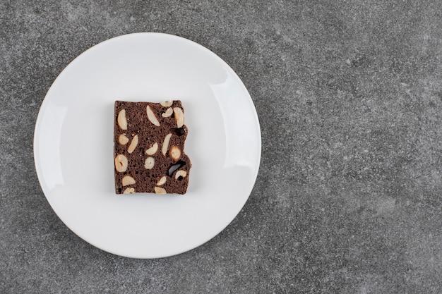 하얀 접시에 신선한 수제 케이크 조각입니다. 땅콩과 초콜릿.