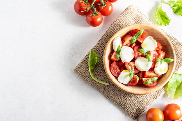 Fresh homemade caprese salad with tomatoes, basil, mozzarella and olive oil on white marble table top view.
