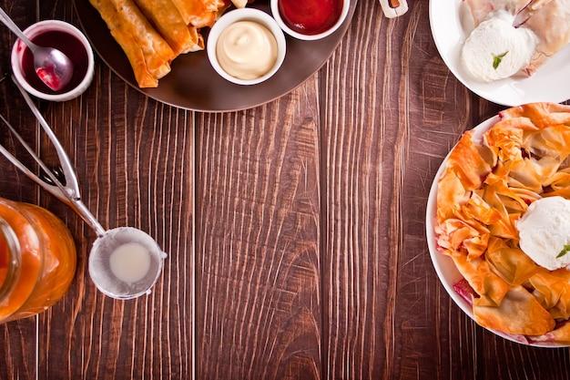 Свежий домашний вишневый пирог из теста filo phyllo с ванильным мороженым, турецкие хрустящие жареные булочки sigara burek на деревянном столе. вид сверху