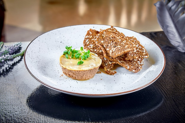 Fresh homemade chicken or duck liver pate with bread, croutons on white plate. dark background. copy space, horizontal. restaurant food. goose liver pate