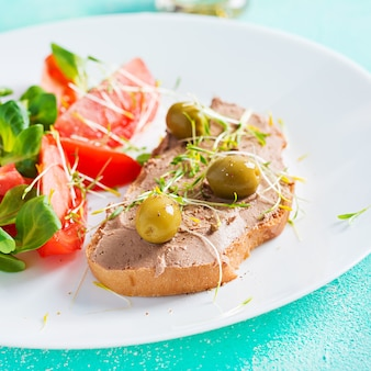 Fresh homemade chicken liver pate on bread and tomatoes salad