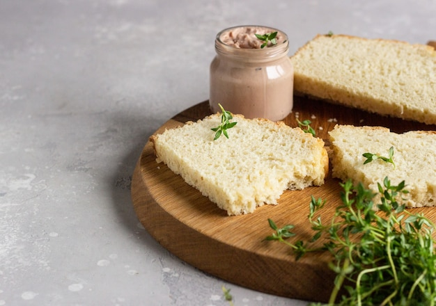 Fresh homemade chicken liver pate on bread with thyme on a wooden cutting board.