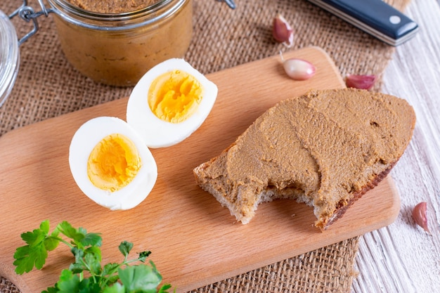 Fresh homemade chicken liver pate on bread on wooden background