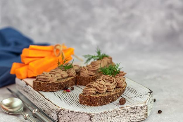 にんじん、玉ねぎ、バターを使った新鮮な自家製鶏レバーのパテ。ディルの小枝を添えて。パンに注油。コンクリートの下の灰色のテーブルの上。