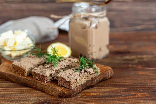 にんじん、玉ねぎ、バターを使った新鮮な自家製鶏レバーのパテ。ディルの小枝を添えて。パンに注油。木製のテーブルの上