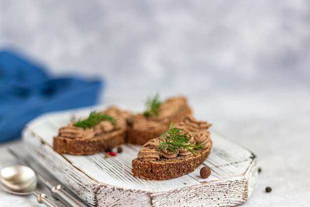 Fresh homemade chicken liver pate with carrots, onions and butter. garnished with a sprig of dill. lubricated on bread. on a gray table under concrete.