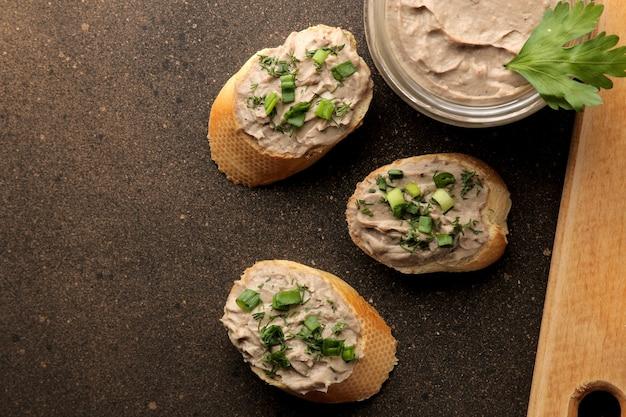 暗い背景のパンに緑の新鮮な自家製鶏レバーのパテ。上からの眺め