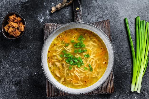 焼きたての自家製チキン スープと麺をテーブルで。黒の背景。上面図。