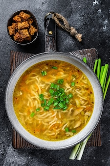 Свежий домашний куриный суп с лапшой за столом. вид сверху.