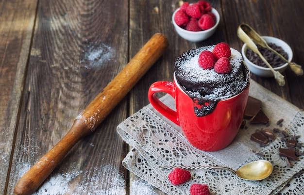 Fresh homemade chocolate cake in mug on rustic wooden background. cooked in microwave.