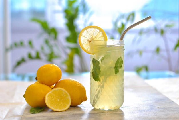 Fresh homemade citrus iced lemonade in transparent glass with lemon slice and mint decoration on marble table