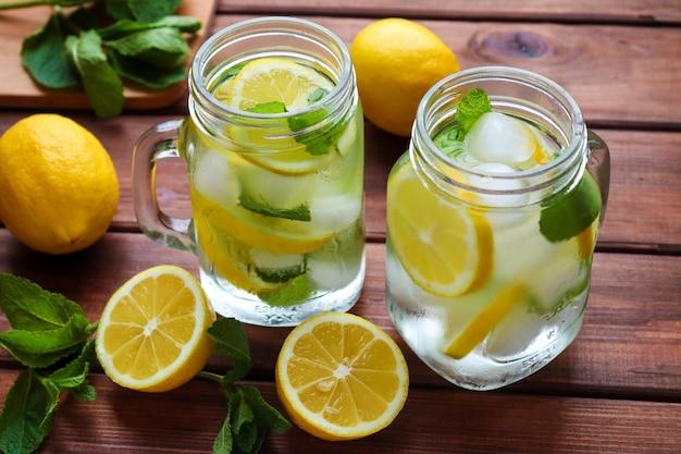 素朴な木製のテーブルにレモンミントと氷を添えた新鮮な自家製柑橘類のレモネード夏の冷たいさわやかな飲み物
