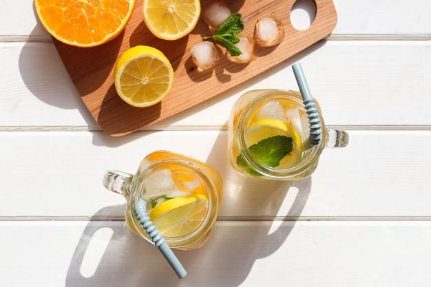 白い木製のテーブルにレモンオレンジミントと氷と新鮮な自家製柑橘類のレモネード