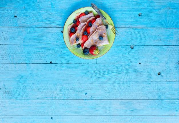 新鮮な自家製クレープは、イチゴとブルーベリーのプレート、明るい青の木製の背景、テキスト用の空き容量で提供しています。