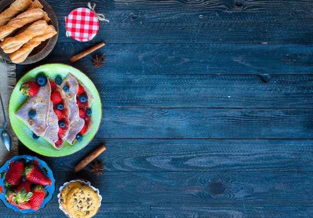 Fresh homemade crepes served on a plate with strawberries and blueberries, on a dark wooden background,