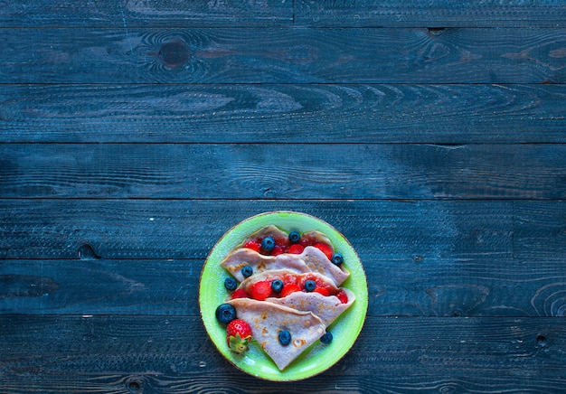 Fresh homemade crepes served on a plate with strawberries and blueberries, on a dark wooden background