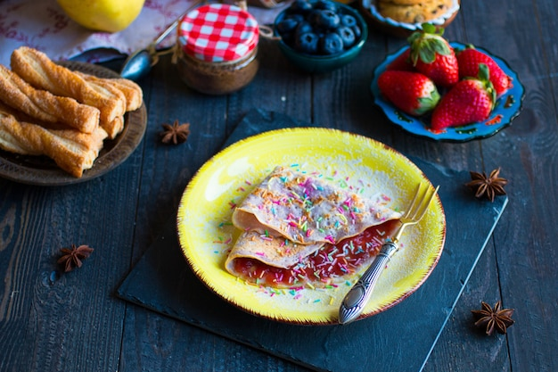 Fresh homemade crepes served on a plate with strawberries and blueberries on a dark wooden background