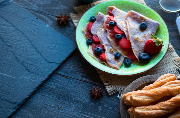 Fresh homemade crepes served on a plate with strawberries and blueberries, on a dark wooden surface,