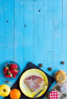 Fresh homemade crepes served on a plate with strawberries and blueberries on a light blue wooden background