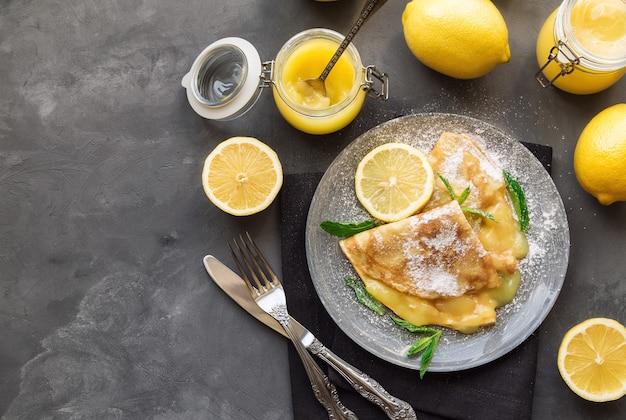 灰色のコンクリートテーブルにレモンカードを添えた新鮮な自家製クレープ。上面図。