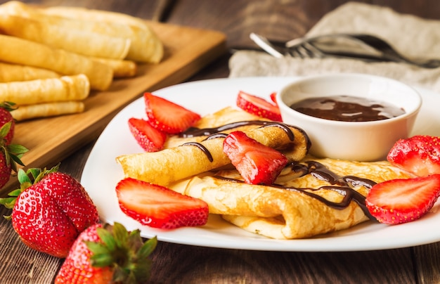 Fresh homemade crepes with strawberries and chocolate sauce on rustic wooden background